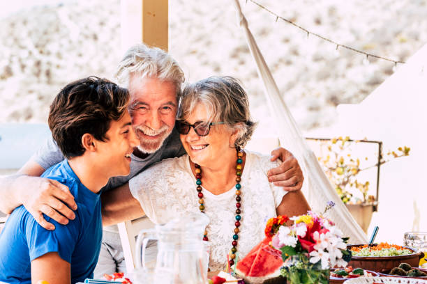 Portrait of people caucasian family with teen and grandfathers smiling and having fun together at home or restaurant eating food - concept of diversity and mixed ages with senior stock photo