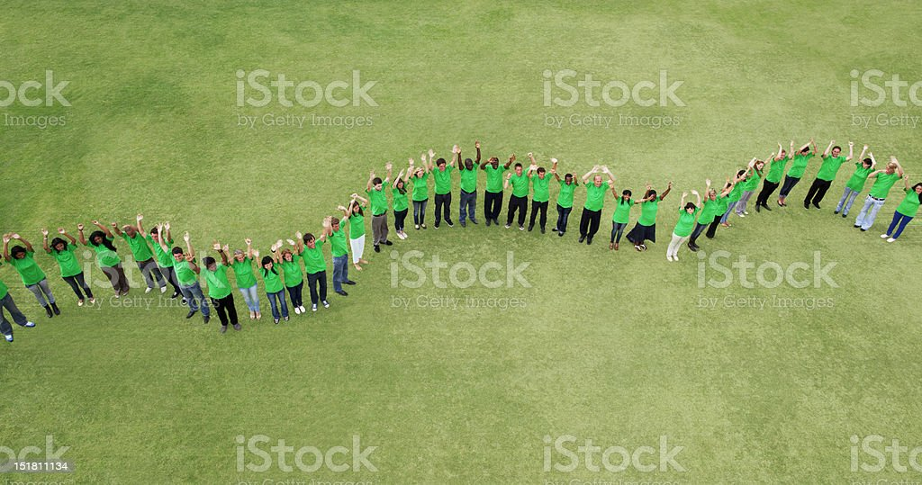 Portrait of people in green t-shirts forming wavy line in field stock photo