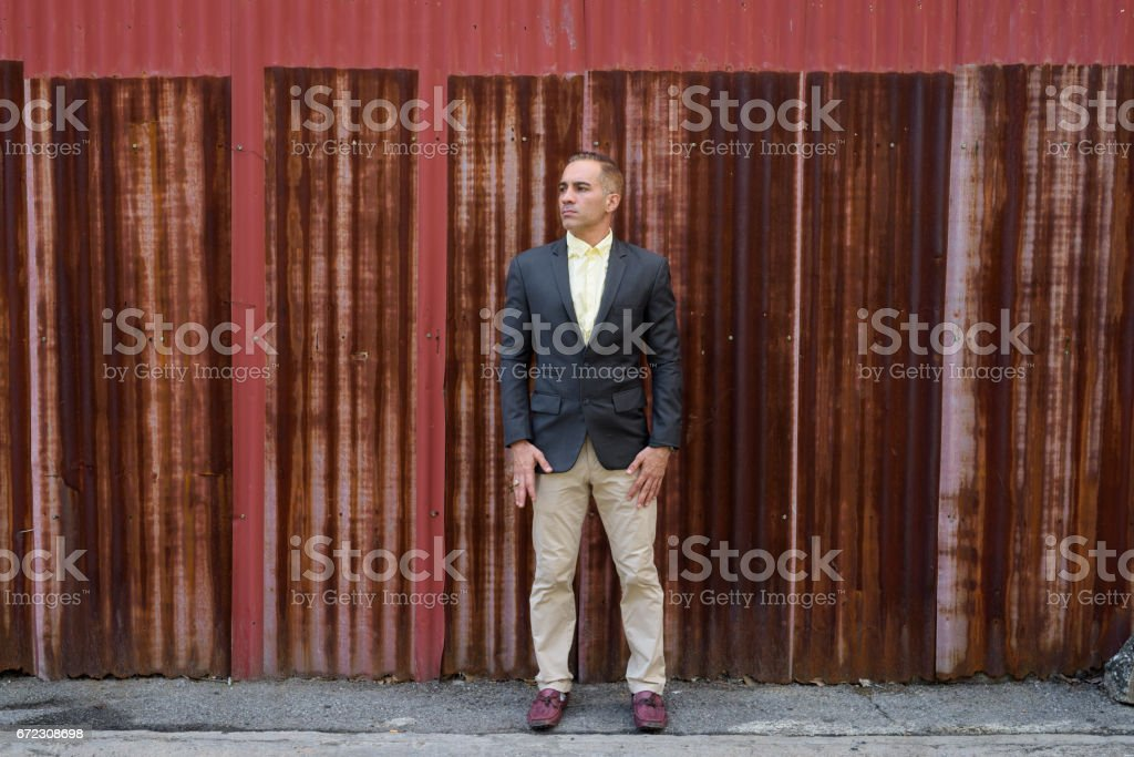 Portrait of Persian businessman standing and thinking against old rust sheet wall stock photo