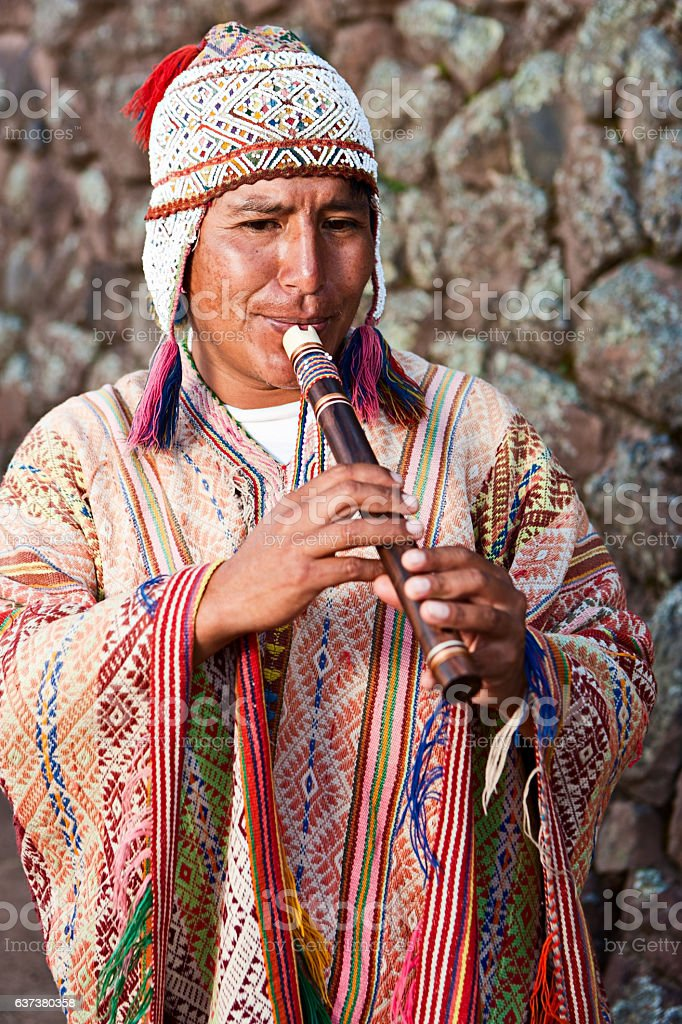Portrait of Peruvian man playing a flute, Inca ruins, Pisac stock photo