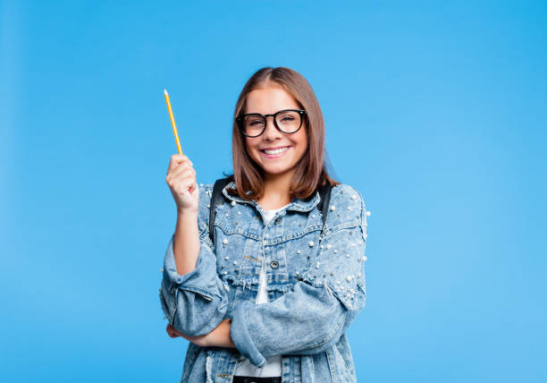 Portrait of petty teenage girl poinitng with pencile stock photo