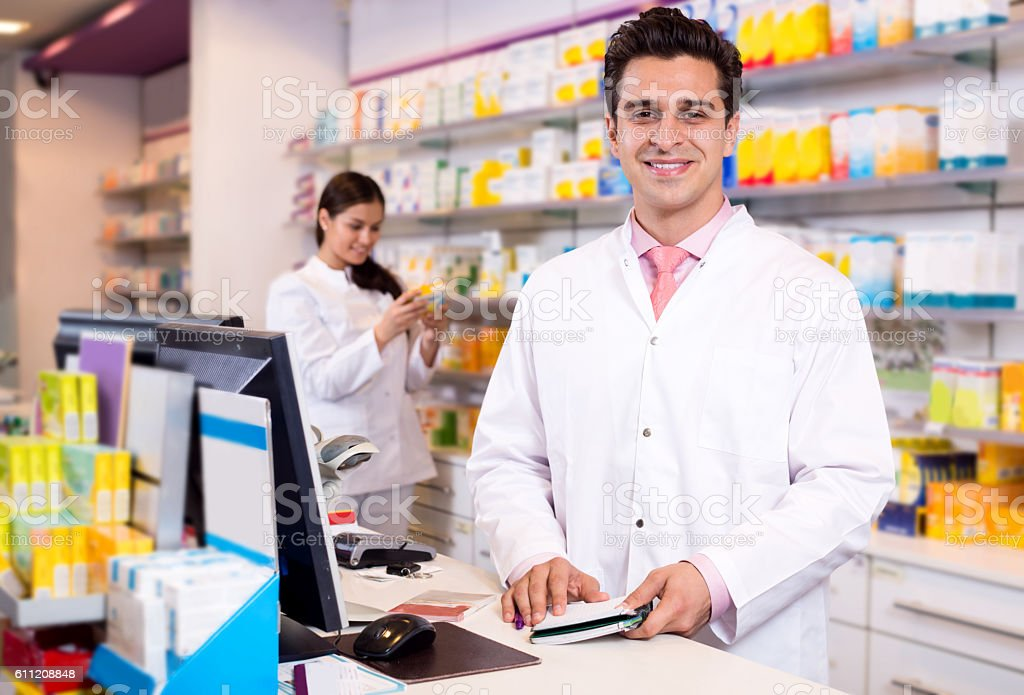 Portrait of pharmacist and assistant working - foto de acervo