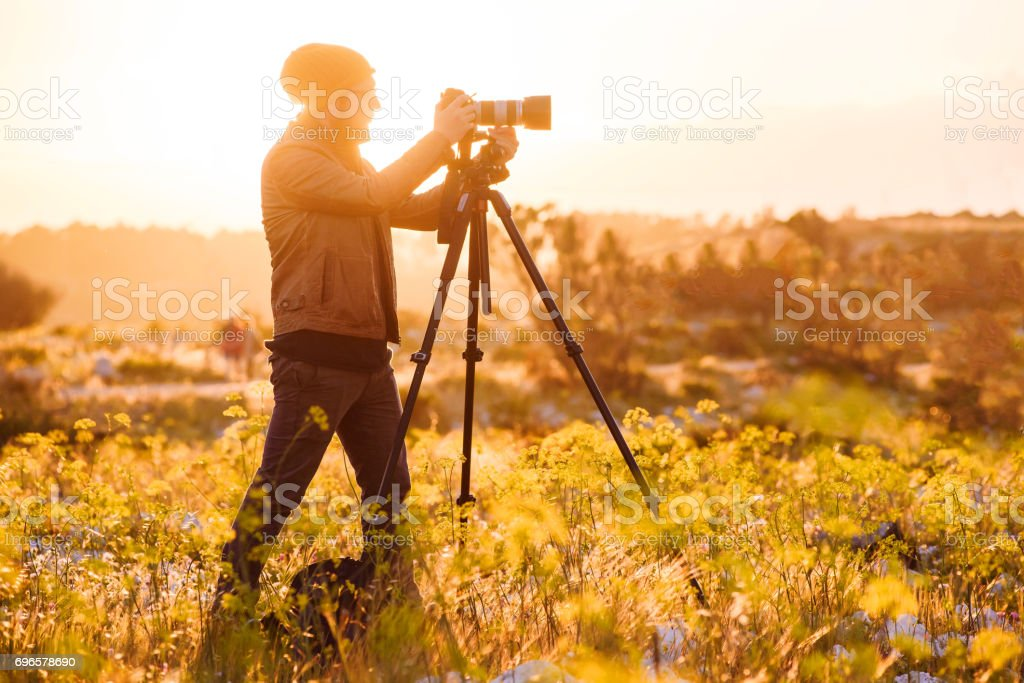 Portrait of photographer making photos with camera on tripod at sunset stock photo