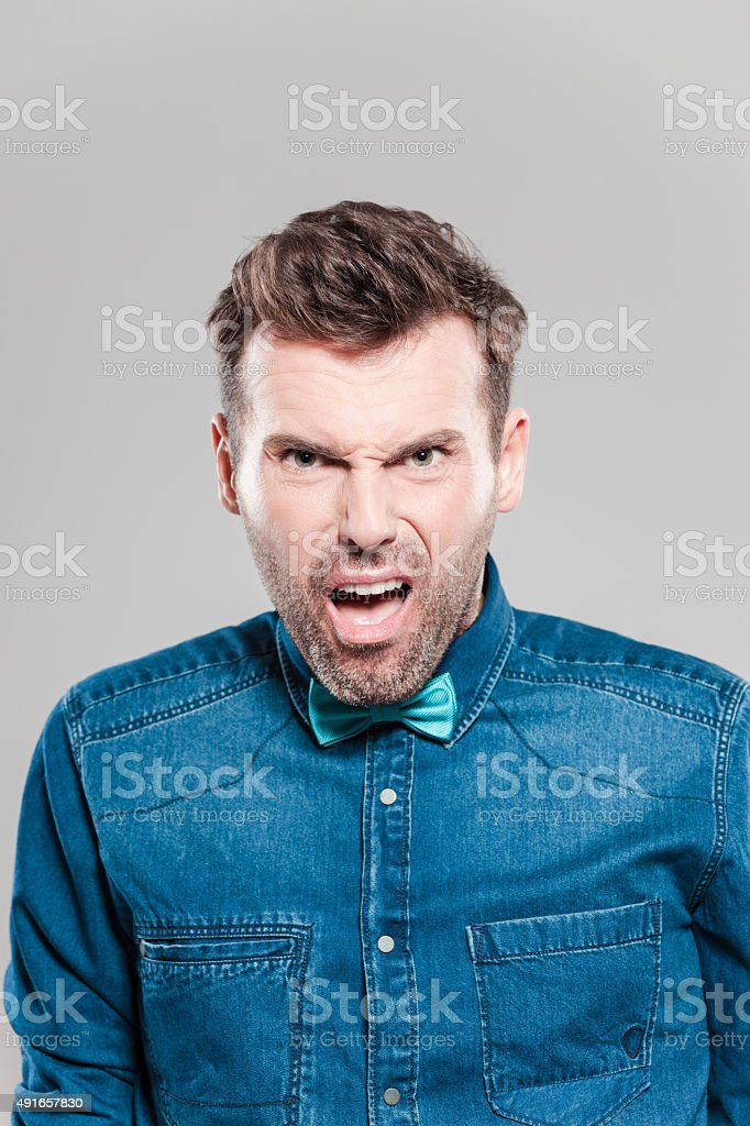 Portrait of pissed man wearing jeans shirt and bow tie Portrait of angry man wearing jeans shirt and bow tie, staring at camera with furious facial expression. Studio shot, grey background. 2015 Stock Photo
