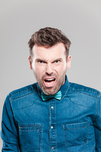 Portrait Of Pissed Man Wearing Jeans Shirt And Bow Tie Stock Photo - Download Image Now