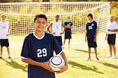 Portrait Of Player In High School Soccer Team Holding Ball Smiling To Camera