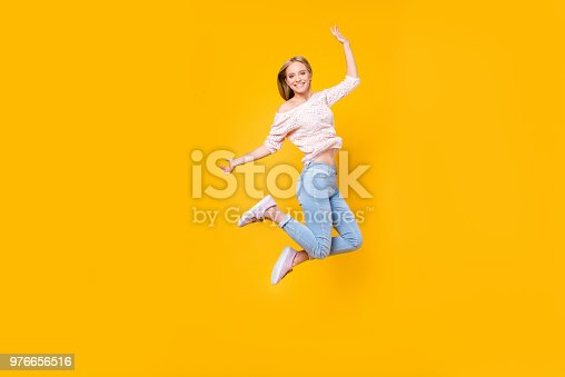 istock Portrait of playful crazy girl jumping in the air looking at camera enjoying weekend having perfect mood isolated on yellow background 976656516