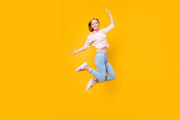 黄色の背景に分離された完璧なムードを持つ週末を楽しんでいるカメラを見て空気中のジャンプ遊び心のある狂気の少女の肖像画 ストックフォト
