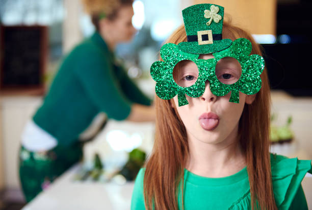 portrait of playful girl celebrating saint patrick's day - happy st. patricks day stock photos and pictures