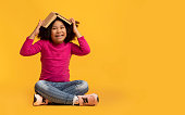Education Concept. Portrait Of Playful Little Afro Girl With Opened Book On Head Sitting On Yellow Background In Studio And Laughing, Copy Space