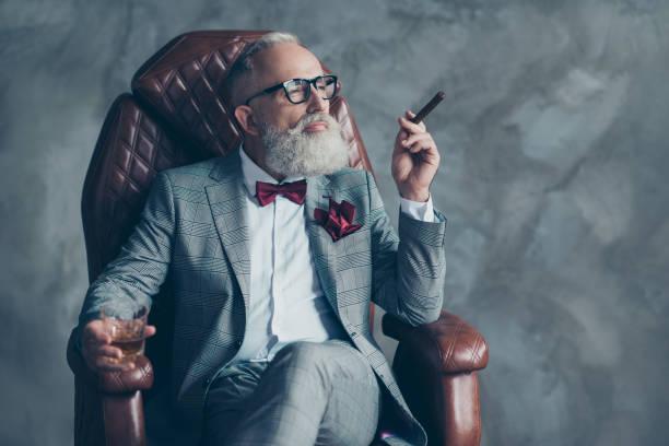 portret van posh chique stijlvol viriel dromerige trendy dromen verzorgd brute groot bedrijf chief miljonair zittend op lederen fauteuil roken sigaret drinken van drank geïsoleerd op een grijze achtergrond - guy with cigar stockfoto's en -beelden