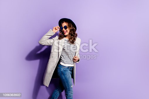 Portrait of positive active girl going in street style striped outfit looking back away holding eyelet of glasses with hand isolated on violet background
