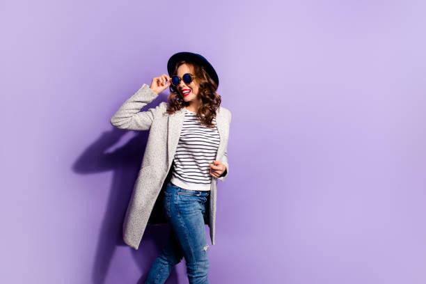 portre pozitif etkin kız sokak stil çizgili kıyafeti geri menekşe arka plan üzerinde izole el ile dış görev holding deliği gözlük arıyor olacak - mont stok fotoğraflar ve resimler