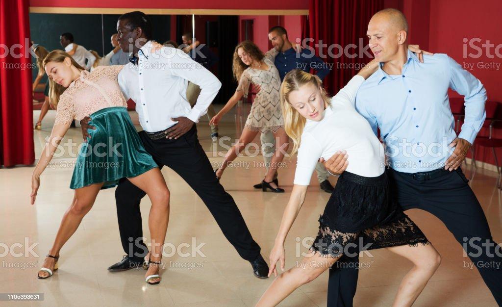 Portrait of positive adult pairs enjoying tango in modern dance hall...
