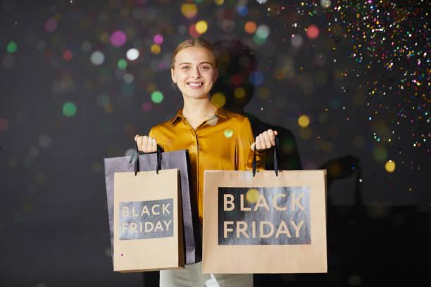 Porträt von positiven schönen Mädchen in stilvollen Outfit hält Einkaufstaschen, während unter fallenKonfetti stehen – Foto