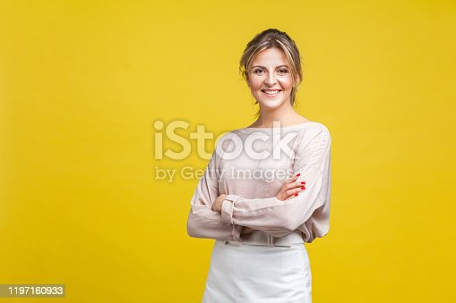 Portrait of positive beautiful young woman with fair hair in casual beige blouse standing with crossed arms and looking at camera, toothy smile. indoor studio shot isolated on yellow background
