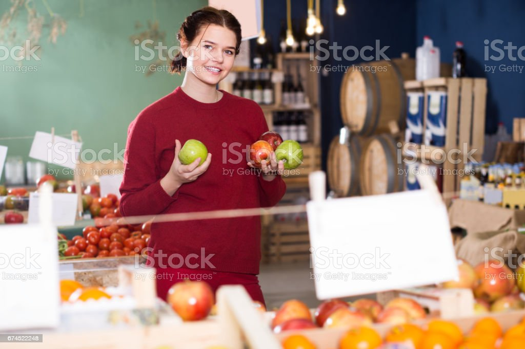 Portrait of positive brunette girl buying apple in supermarket stock photo