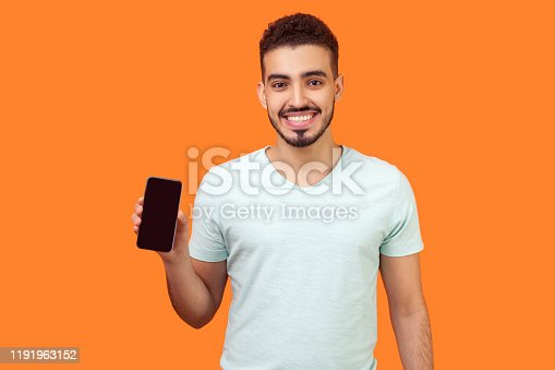 istock Portrait of positive brunette man holding cellphone and smiling, looking satisfied with mobile data tariffs. isolated on orange background 1191963152