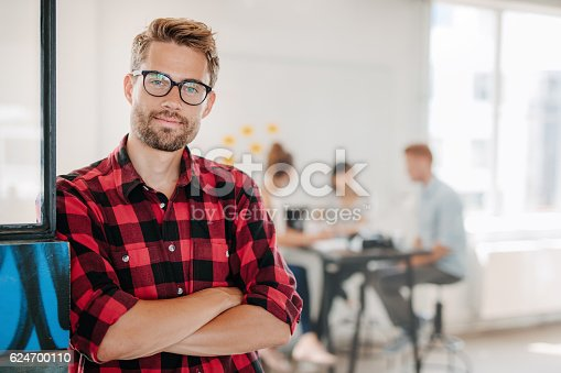 istock Portrait of positive businessman in office 624700110