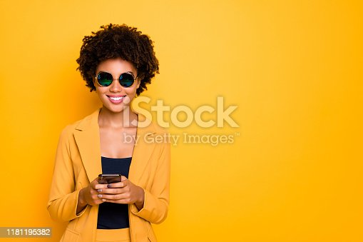 Portrait of positive cheerful afro american girl in sunglass use her smartphone, type text post comments feedback read feednews wear stylish trendy suit clothes isolated over yellow collor background