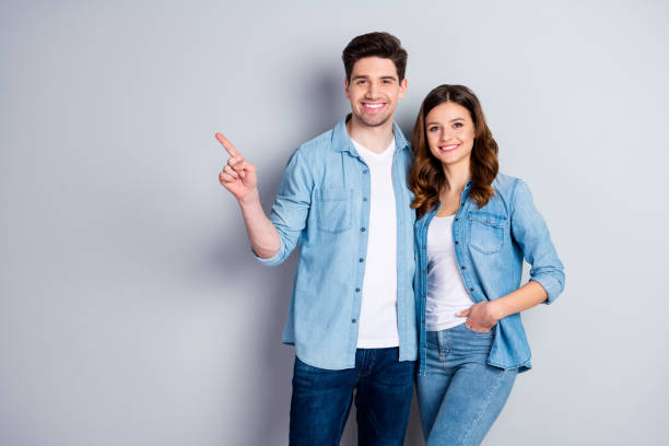 Portrait of positive cheerful couple spouse point index finger present advert promotion wear casual style clothes isolated over gray color background stock photo