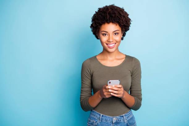 Retrato de piel oscura alegre positiva chica use sostener su teléfono inteligente disfrutar de entradas de blog comentarios llevan traje verde aislado sobre fondo de color azul - foto de stock