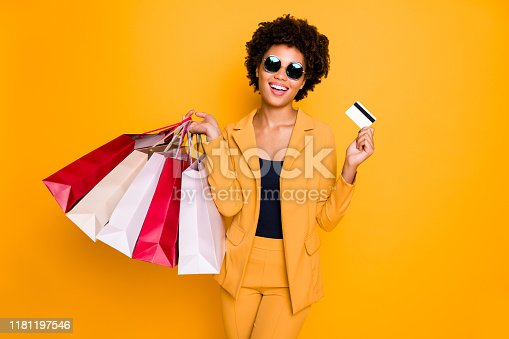 istock Portrait of positive cheerful dark skin shopper on leisure time hold credit card buy many bags went shopping wear style pants trousers sunglass isolated over yellow color background 1181197546