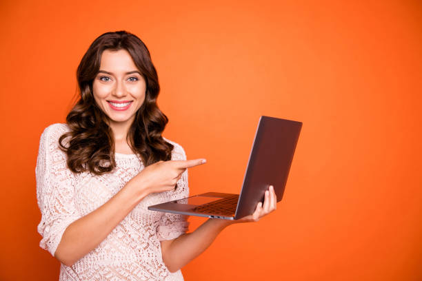 Portrait of positive cheerful girl use laptop search online black friday bargain point index finger website promo wear good looking clothing isolated over shine color background stock photo