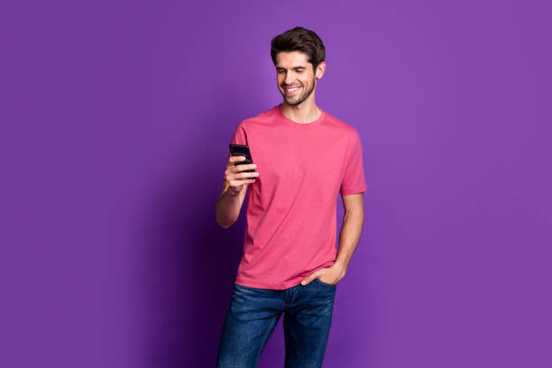 Portrait of positive cheerful guy use cell phone enjoy chatting repost share social network information wear style stylish trendy outfit isolated over bright shine color background stock photo