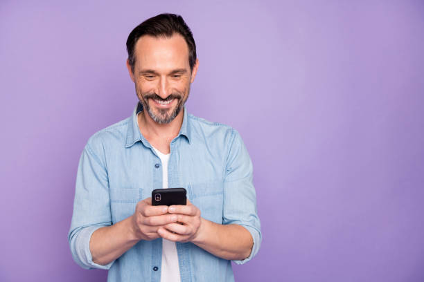 Portrait of positive cheerful man use smart phone chatting blog post follow bloggers share social media information wear good looking clothing isolated over violet color background stock photo