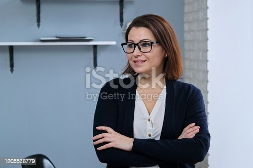 949435100 istock photo Portrait of positive confident mature woman with folded arms 1205536779