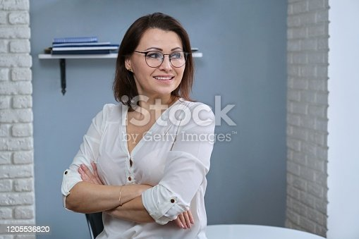 949435100 istock photo Portrait of positive confident mature woman with folded arms 1205536820