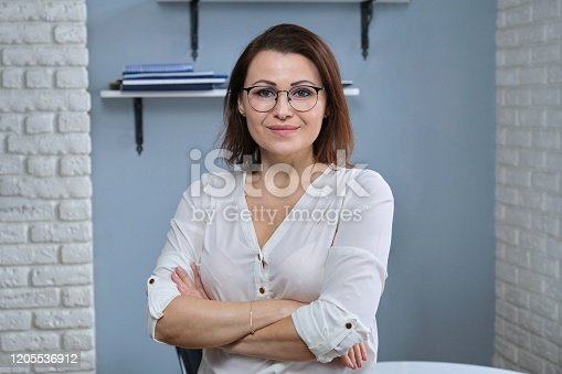 949435100 istock photo Portrait of positive confident mature woman with folded arms 1205536912
