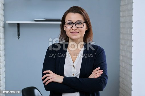 949435100 istock photo Portrait of positive confident mature woman with folded arms 1205536976