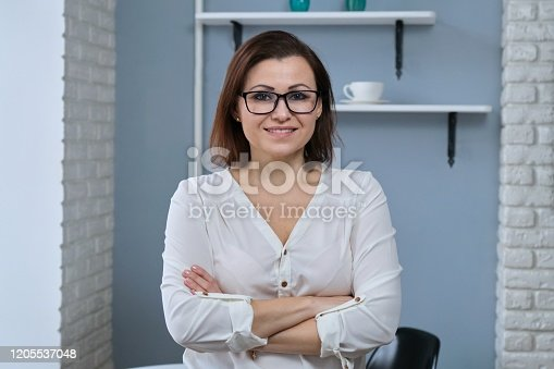 949435100 istock photo Portrait of positive confident mature woman with folded arms 1205537048