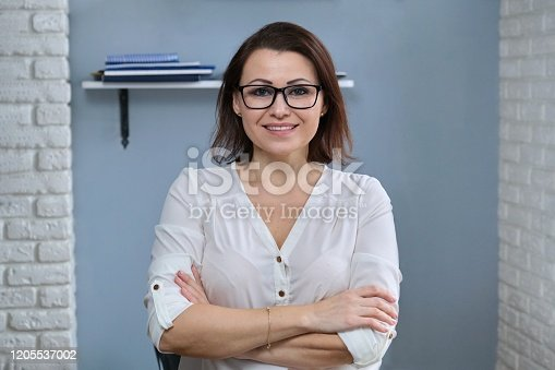 949435100 istock photo Portrait of positive confident middle aged woman with arms crossed 1205537002
