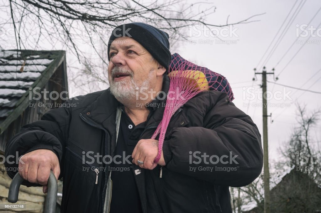Portrait of positive elderly peasant with walking stick carrying some stuff in stringed bag royalty-free stock photo