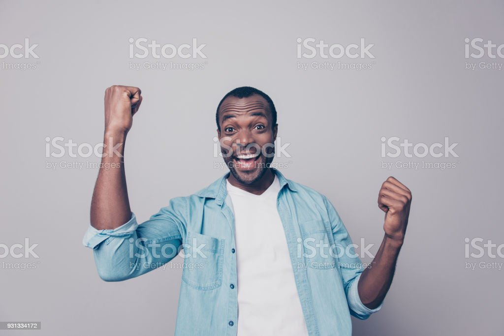 Portrait of positive, happy, shouting, screaming, laughing man with open mouth and raised arms, celebrating successfully completed work, isolated on grey background stock photo