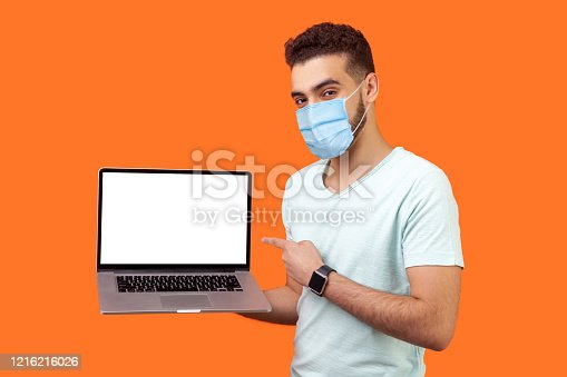 istock Portrait of positive joyful brunette man with surgical medical mask standing holding laptop with blank screen and smiling at camera, internet advertising. 1216216026