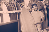 Portrait of cheerful positive  man with board for surfing in the shop