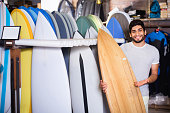 Portrait of happy cheerful   man with board for surfing in the shop