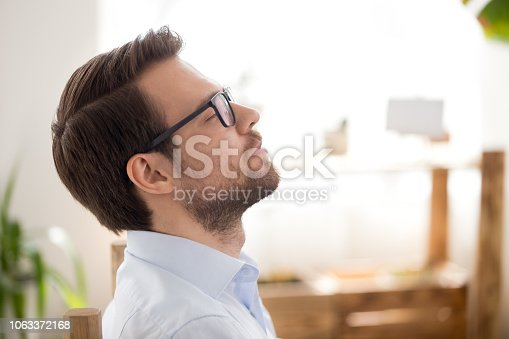 istock Portrait of positive man with closed eyes in office 1063372168
