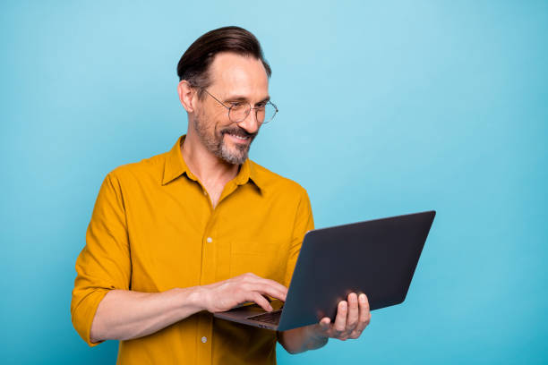 Portrait of positive man worker work on his computer text with his family colleagues wear yellow shirt isolated over blue color background stock photo