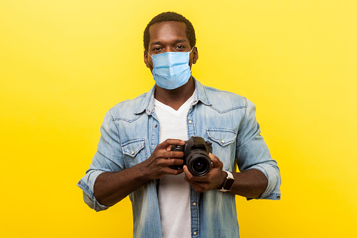 Portrait of positive photographer, man with medical mask holding professional digital dslr camera and looking with toothy smile, enjoying his job.