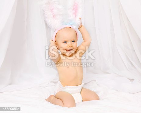 1084486306 istock photo Portrait of positive smiling baby in easter bunny ears 487206534