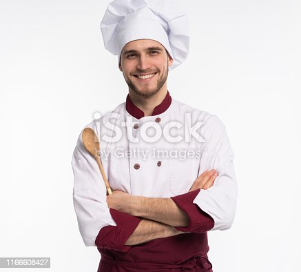 istock Portrait of positive toothy chef cook in beret, white outfit having tools in crossed arms looking at camera isolated on white background. 1166608427