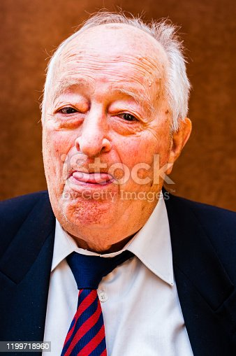 Portrait of positive white elderly man with dark suit, white shirt and striped blue red tie showing his tongue with one eye on bright brown background