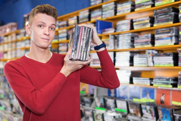 porträt von positiven jungen mann mit stapel von dvds in händen - cd ständer stock-fotos und bilder