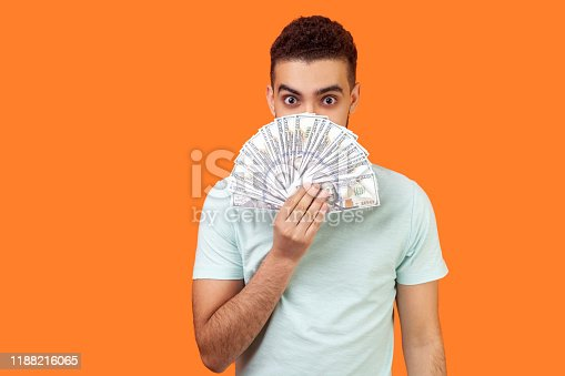istock Portrait of positive young man in white t-shirt hiding half face with dollar. studio shot isolated on orange background 1188216065