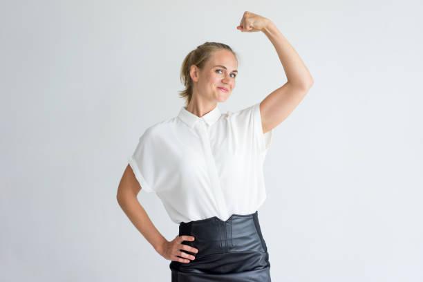 portrait de jeune positive montrant les biceps - directrice photos et images de collection